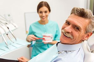 An elderly man receiving implant supported dentures