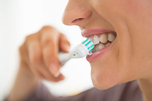 Woman using an electric tooth brush to brush her teeth