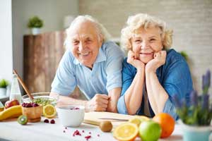 A senior couple in their kitchen smiling with new dentures