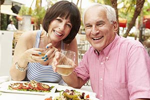 A senior couple enjoying dinner outside and smiling with new porcelain veneers