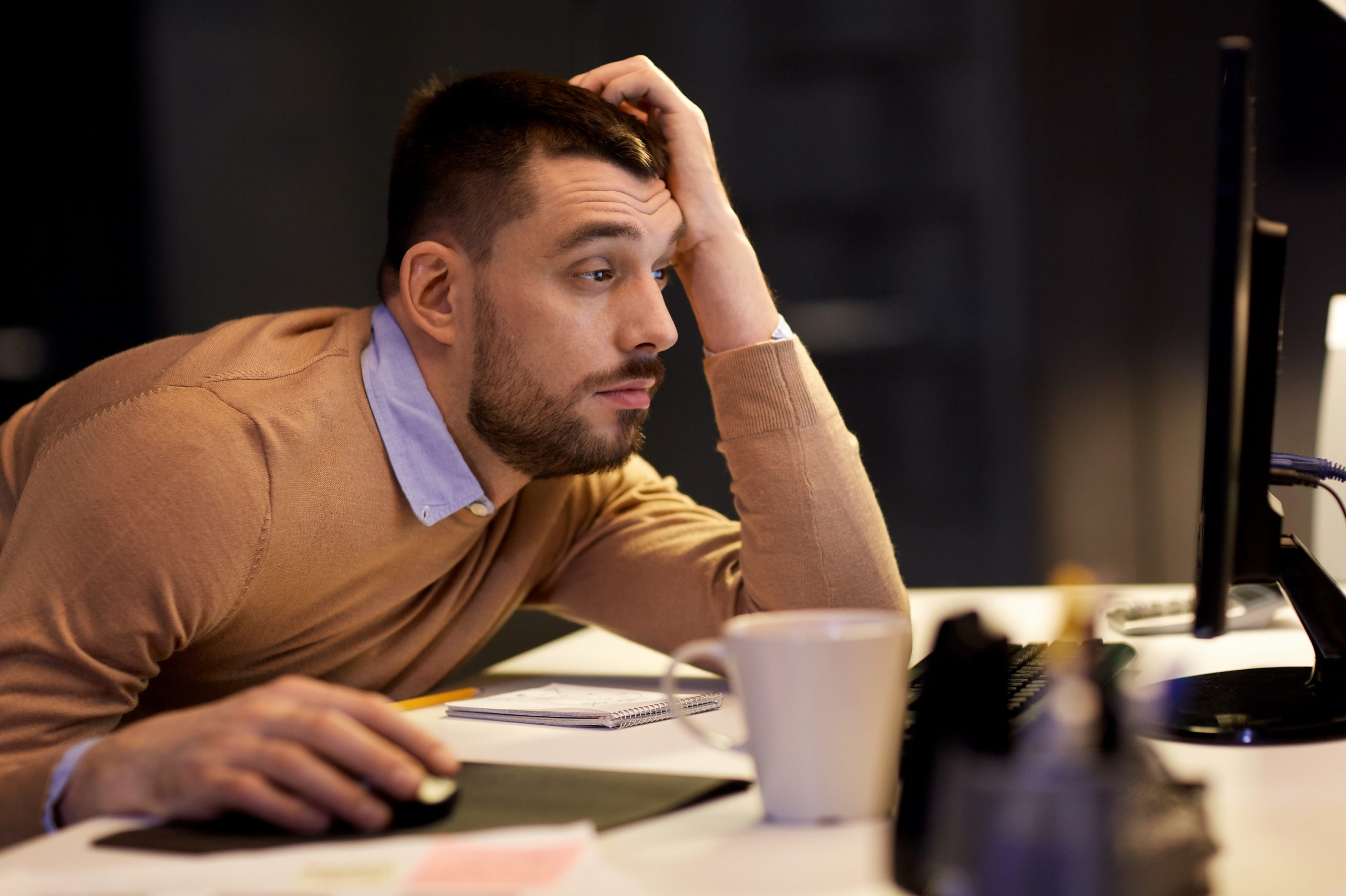 Man suffering from sleep apnea while trying to work on a computer