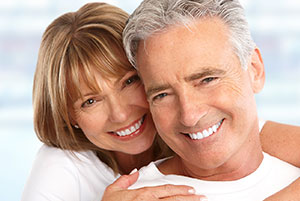 A handsome mature couple smiling after receiving plaque removal