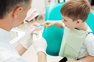 Dentist demonstrating how to brush teeth with a young boy patient