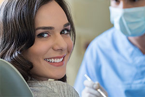 Female dental patient smiling while sitting in dental chair