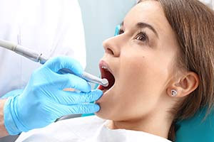 Female dental patient receiving a root canal