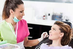 Female dental patient being checked for TMJ disorder