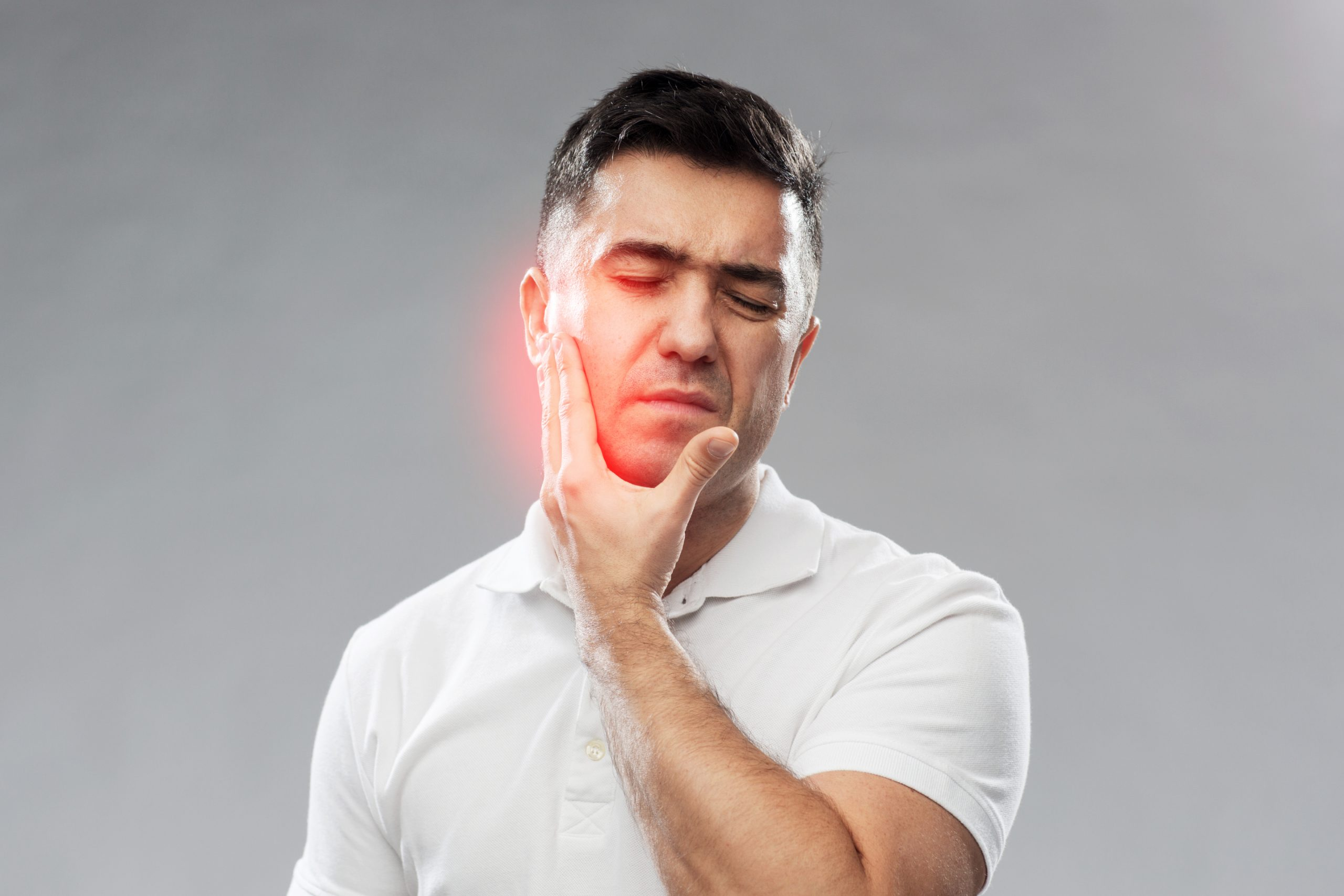 man holding jaw in pain to illustrate what does teeth grinding sound like