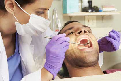 Dentist examining a patient for sleep apnea diagnosis