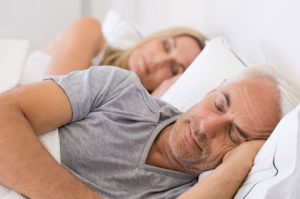 Man sleeping on a bed with his wife