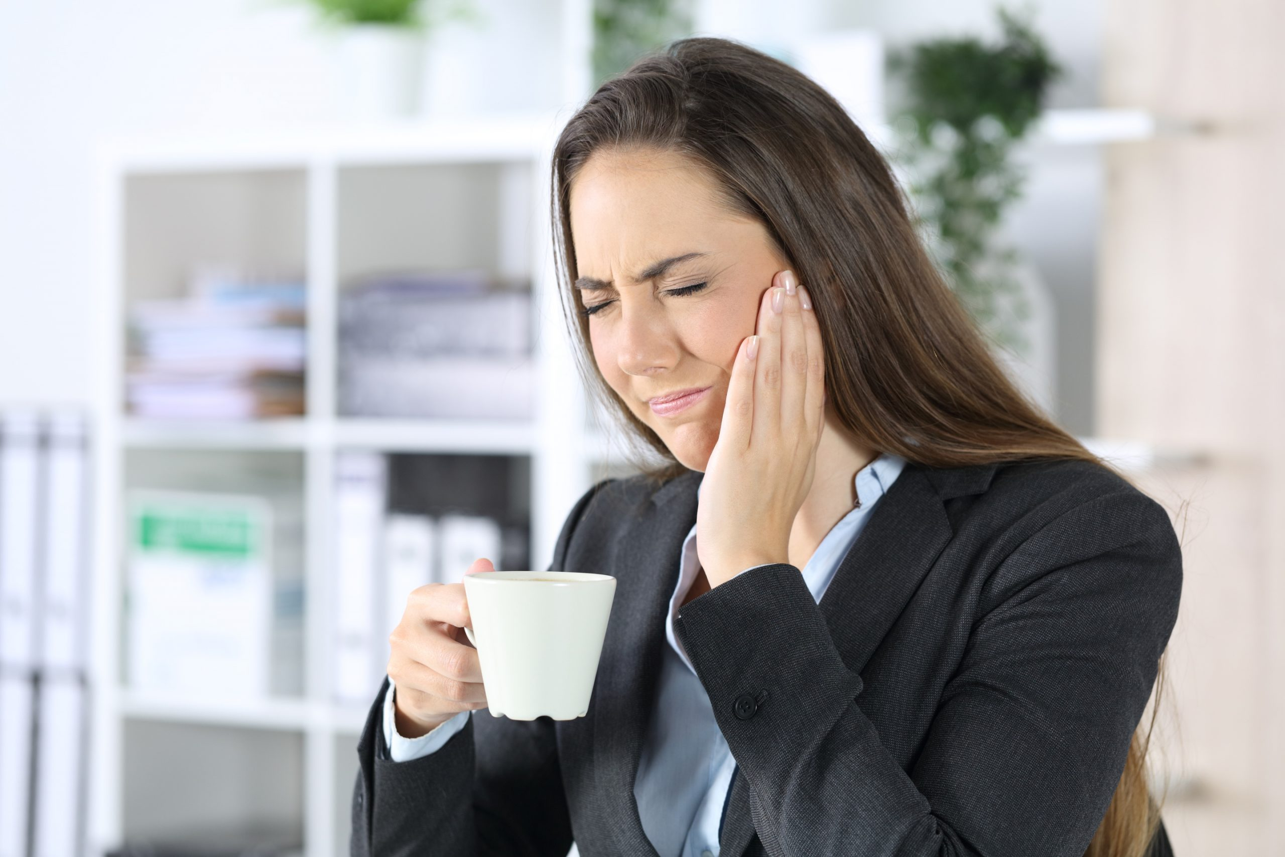 Woman suffering from TMJ trying to drink cofee