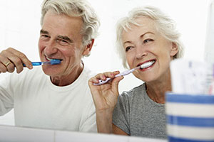 An elderly couple brushing their teeth together