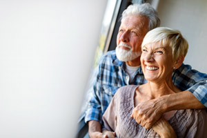 An elderly couple smiling and looking out a window
